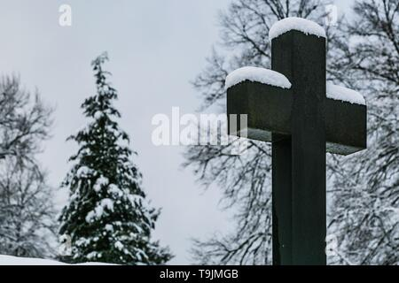 Winter scene of Christian stony cross at a cemetery and trees in the background covered with snow. - Stock Photo