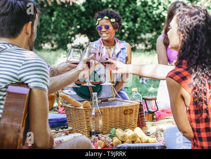 Group of happy friends cheering glasses of red wine at pic nic barbecue in garden - Young people having fun during a weekend day - Stock Photo