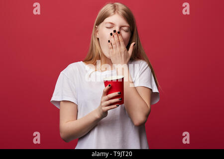weak young woman with closed eyes yawning, closing her mouth with palm, trying not to fall asleep in the morning. Monday,close up photo. isolated red background - Stock Photo