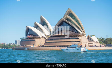 SYDNEY, AUSTRALIA - FEBRUARY 11, 2019: A motor boat passing Sydney Opera House, one of Australia's most recognisable building. - Stock Photo