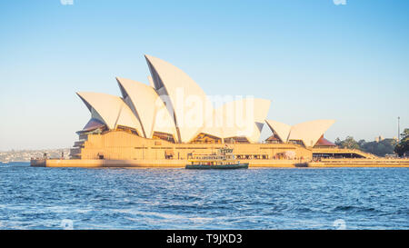SYDNEY, AUSTRALIA - FEBRUARY 11, 2019: A ferry passing Sydney Opera House in the late afternoon. - Stock Photo