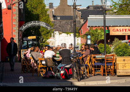 Outdoor cafe restaurant Ireland. People enjoying the sunny warm weather outside a bar restaurant at the Old Market Lane in Killarney, County Kerry. - Stock Photo