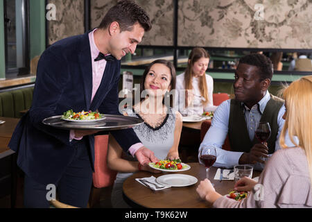 Polite smiling waiter bringing ordered dishes to guests of restaurant - Stock Photo