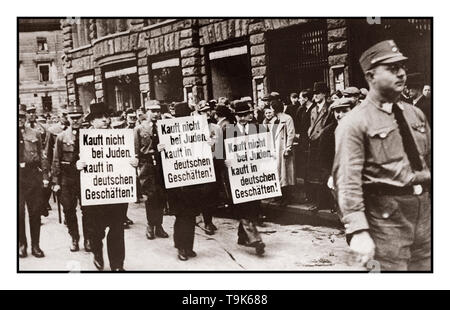 1930's Boycott Jewish owned stores Anti Jewish racist Nazi propaganda image 1930's Three Jewish businessmen are paraded down Bruehl Strasse by uniformed Nazi NSDAP Brown Shirts in central Leipzig, carrying signs that read: 'Don't buy from Jews; Shop at German stores!' Leipzig Germany - Stock Photo