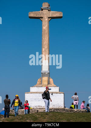 People taking photos and selfies in front of the summit cross of peak Olarizu, Vitoria, Spain - Stock Photo