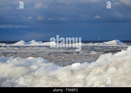 Wind-blown lake ice piled up near the shore of Lake Peipsi in spring, breaking up as it thaws, Estonia, April. - Stock Photo