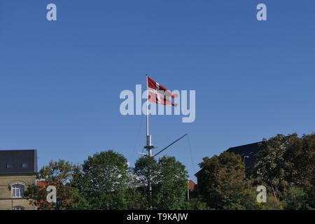 The national flag of Denmark on a mast at the Copenhagen harbor, Denmark - Stock Photo