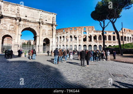 Rome, Italy - December 29, 2014: View of the Arch of Constantine and the Colosseum from Via dei Fori Imperiali, around some tourists and photographers - Stock Photo