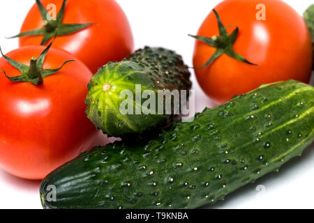 Fresh vegetables green cucumbers and red tomatoes on white isolated background, closeup. Healthy diet, vegetarian food - Stock Photo
