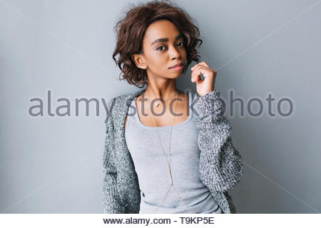 Young beautiful brown girl with short curly hairstyle on gray background. Wearing casual clothes - gray cardigan, knitted jacket, shirt, long stylish necklace with triangle. - Stock Photo