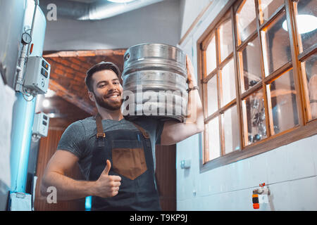 A young brewer in an apron holds a barrel with beer in the hands of a brewery. - Stock Photo