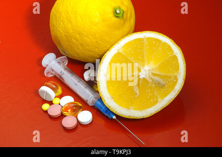 Lemons on a red background with syringes and pills. Medical preparations and vitamin C. Subcutaneous injectors with tablets side by side with lemons o - Stock Photo