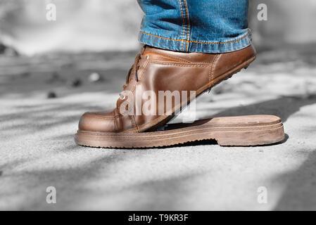 Torn men's shoes in the street. Torn shoe on foot. Footwear requiring repair - Stock Photo