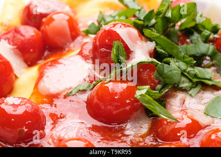 Red cherry tomato sauce with basil as close-up - Stock Photo