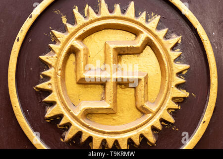 Swastika carved and drawn on a rock of temple, an ancient solar hinduism symbol in the Indian culture, India, Varanasi - Stock Photo