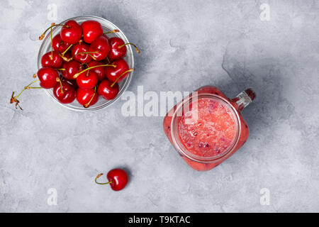 smoothies sweet cherry in a mason jar, fresh sweet cherry on a gray concrete background. view from above - Stock Photo