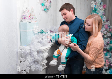 loving parents show their baby Christmas gifts . the concept of Christmas - Stock Photo