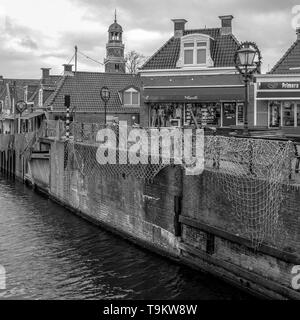 NETHERLANDS - LEMMER - JANUARY 12, 2019: Sluice and buildings in the center of Lemmer in a black and white photo in Friesland, Netherlands. - Stock Photo