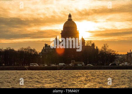 Sunrise behind Saint Isaac's Cathedral in Saint Petersburg on a winter morning with Neva river in foreground (St. Petersburg, Russia, Europe) - Stock Photo