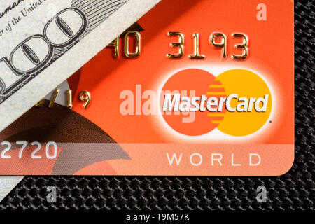 Lviv, Ukraine - 26 April 2019 : A red card with a MasterCard logo is placed on a one hundred dollar banner close-up 2020 - Stock Photo