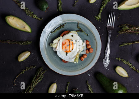 Top view of healthy breakfast scrambled eggs with bread and nuts in a plate on black background with avocado, rosemary, lime. Top view. Flat lay. Heal - Stock Photo