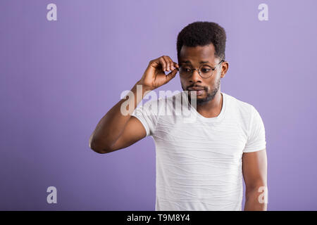 Wow, It's incredible. Close up portrait of young bearded dark skinned man touching the spectacles and looking down with amazed shocked expression agai - Stock Photo