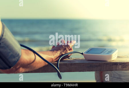 Hypertensive patient performing an automatic blood pressure test on the beach / man's self-control of blood pressure with a tensiometer on the outside - Stock Photo