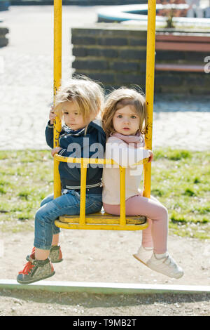 Brother and sister on swing on sunny day - Stock Photo