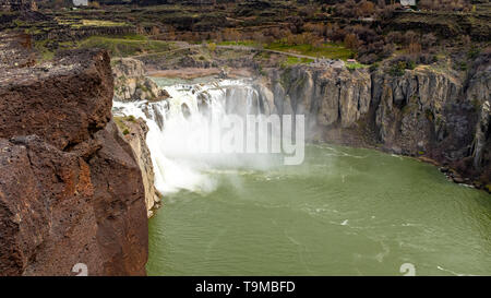 Spring runoff on the Snake river over Shoshone Falls with rocky cliffs - Stock Photo