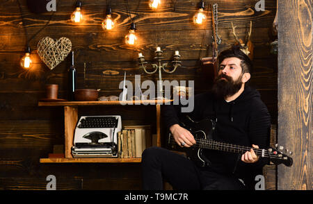 Involved in relaxation. Man bearded musician enjoy evening with bass guitar, wooden background. Man with beard holds black electric guitar. Guy in - Stock Photo