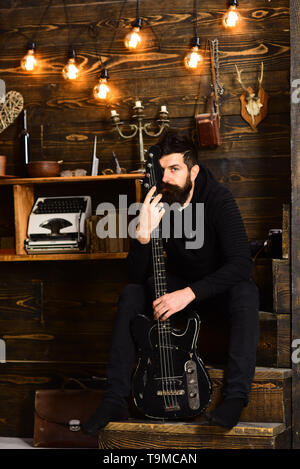 Connection through music. Man bearded musician enjoy evening with bass guitar, wooden background. Guy sits thoughtful dreamy in cozy warm atmosphere - Stock Photo