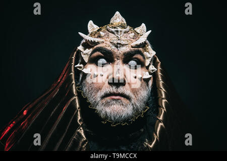 Blind wizard in metallic hood with surprised look absorbed by darkness, magic and fantasy concept. Demon head with sharp thorns and warts on black - Stock Photo