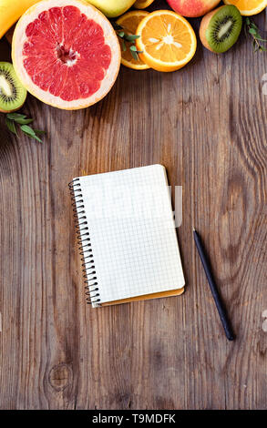 Fresh summer fruits and notebook on brown wooden background, healthy organic food orange kiwi grapefruit on table, detox diet concept, vitamin nutriti - Stock Photo