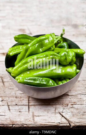 Fresh green raw peppers in metal bowl on rustic wooden table background. Vegan green food. - Stock Photo