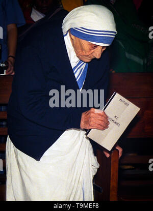 Mother Teresa holding a booklet with the names of sisters taking their vows to the Missionaries of Charity in 1995 - Stock Photo