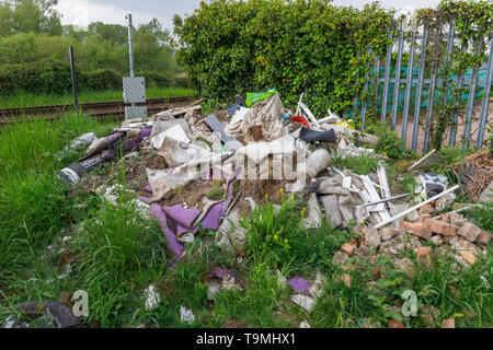 A pile of rubbish, rubble and trash from illegal fly tipping dumped beside a railway line in Nursling, Test Valley, Southampton, Hampshire, UK - Stock Photo