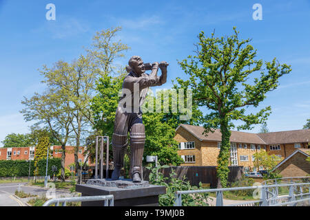 Bronze statue of cricket player Eric Bedser on Bedser Bridge, a footbridge on the Basingstoke Canal linking the WWF-UK headquarters to the town centre - Stock Photo