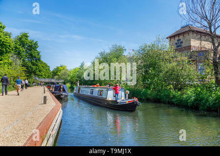 Narrowboat on the Basingstoke Canal passing through Woking town centre near the New Victoria Theatre, Surrey, southeast England on a sunny day - Stock Photo