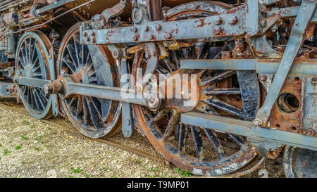 Rusty wheels on a old steam locomotive sitting abandoned in a rail yard decaying away - Stock Photo