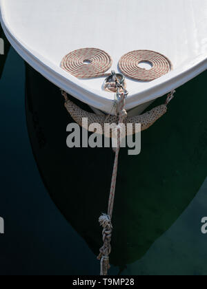 Bow of a small white fishing boat with ropes in Croatia - Stock Photo