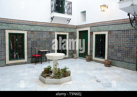 Islamic architectural motifs and tile work in the open-air courtyard of a traditional 16th century home in the medina (old city) of Tunis, Tunisia. - Stock Photo