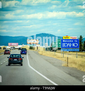 Big blue 'Welcome to Idaho' roadway sign off of Interstate 90 heading East from Washington State, USA - Stock Photo