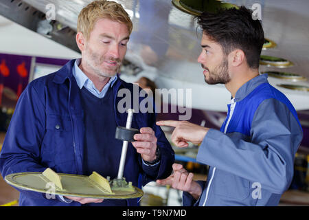 male aero engineer carrying out check in hangar - Stock Photo