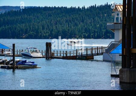 A floatplane readies for take off on Lake Coeur d'Alene, near floating Resort boardwalk with alpine mountain views in Coeur d'Alene, ID - Stock Photo