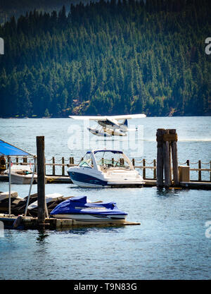 A sightseeing floatplane takes off on Lake Coeur d'Alene, near the floating boardwalk around the Resort's marina with alpine and mountains in the back - Stock Photo