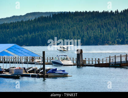 A floatplane takes off on Lake Coeur d'Alene, near the floating boardwalk around the Resort's marina with alpine mountain view in Coeur d'Alene, ID, - Stock Photo