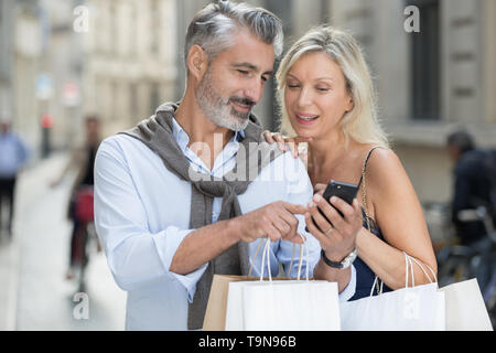 mature couple taking selfie outdoors with smart phone - Stock Photo