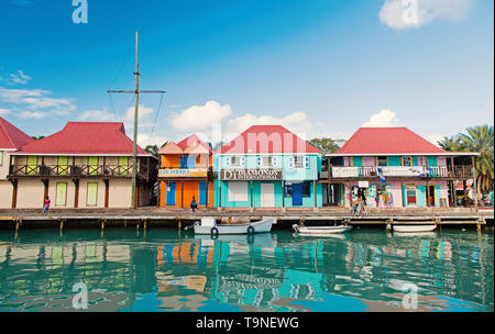 St johns, Antigua - March 05, 2016: boats docked in sea at village quay with houses on blue sky. Summer vacation on tropical island. Discovery and adv - Stock Photo