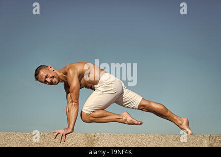 Man practicing yoga blue sky background. Reached peace of mind. Meditation and yoga concept. Yoga helps find balance. Practice asana outdoor. Yoga pra - Stock Photo
