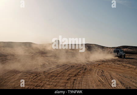 Competition racing challenge desert. Car overcome sand dunes obstacles. Car drives offroad with clouds of dust. Offroad vehicle racing obstacles in wi - Stock Photo